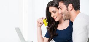Usmívá se spokojený pár při nákupu online kreditní kartou.
