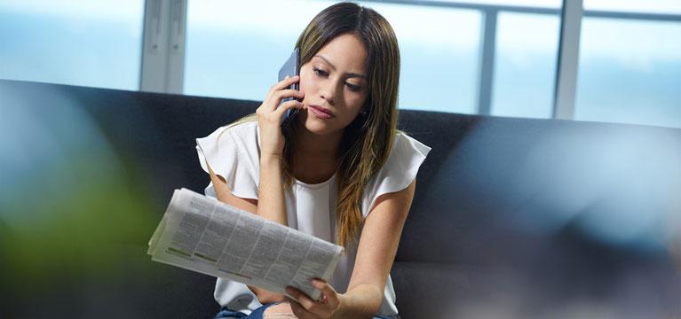 Nezaměstnaná žena hledá práci v novinách.